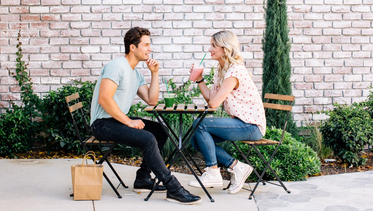 two people at a table drinking smoothies